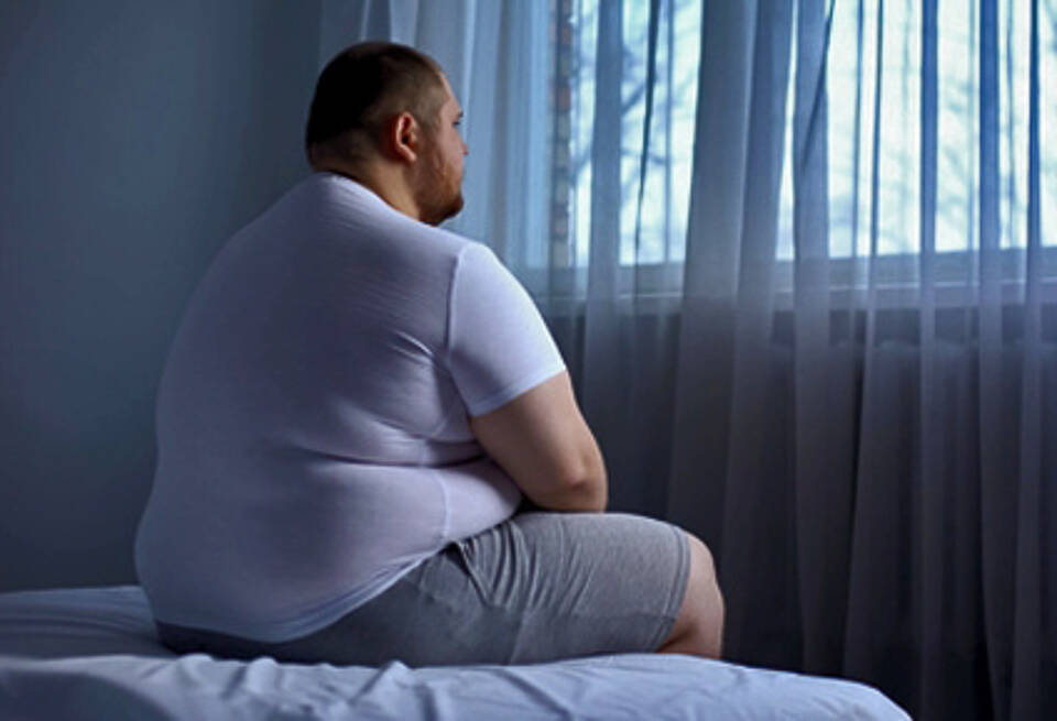 Übergewichtiger Mann sitzt deprimiert auf dem Bett