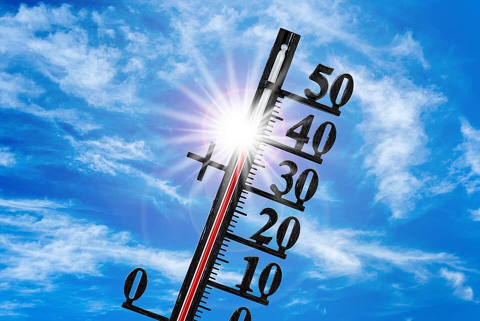 Thermometer mit transparenter Skala bis 50 Grad vor blitzender Sommersonne.