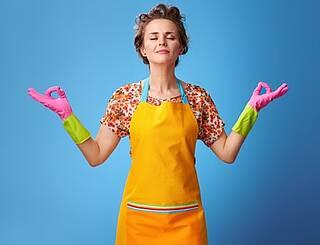 Hausfrau mit Gummischürze und -handschuhen mit Meditationsgestik