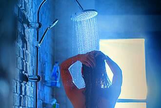 Frau im Bad unter einer Tropenregen-Dusche.