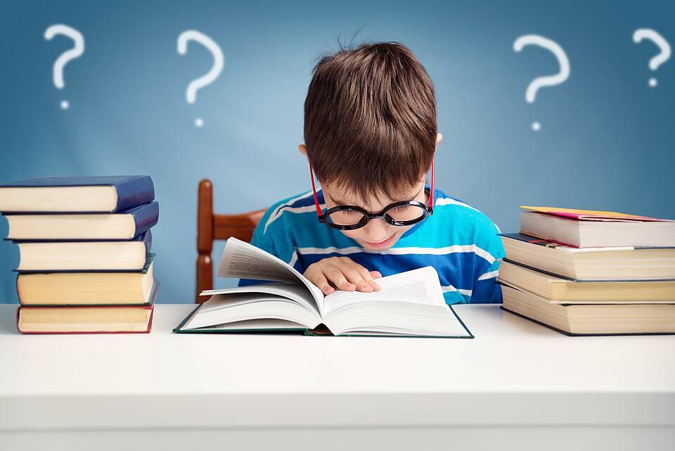 Schuljunge mit dicker, schwarzer Brille, in ein Buch vertieft, links und rechts Bücherstapel