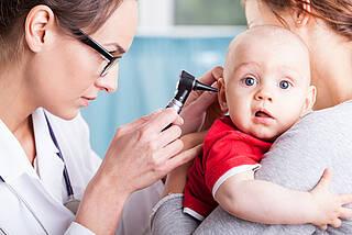 Der Arzt untersucht Babys Ohr mit dem Otoskop