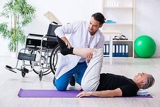 Mann liegt auf Gymnastikmatte, Arzt im weißen Kittel mobilisiert Kniegelenk