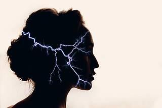 Kopfschmerz - visualisiert als Gewitter-Blitz im Kopf bei einer Frau.
