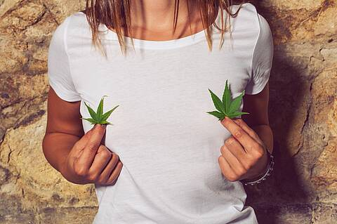 Junge Frau mit weißem T-Shirt hält in jeder Hand ein Cannabis-Blatt.