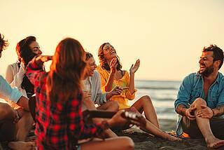 Clique am Strand mit Gitarre in der roten Abendsonne.