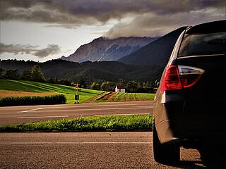 Auto steht in einem Alpental am Straßenrand.