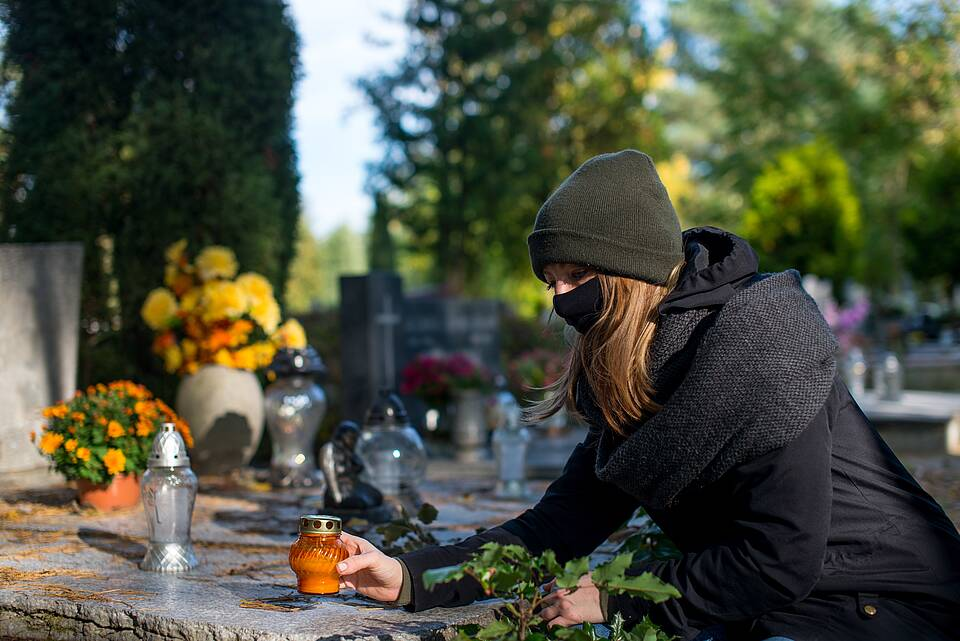 Junge Frau mit Corona-Maske zündet auf einem Friedhof ein rotes Grablicht an.
