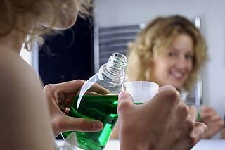 Frau schenkt sich grüne Mundspülung in Becherchen ein.