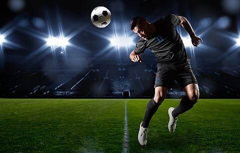 Fußballstadion, Flutlicht: Profifußballer köpft.