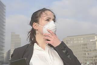 Frau in der Stadt mit Schutzmaske gegen Luftverschmutzung.