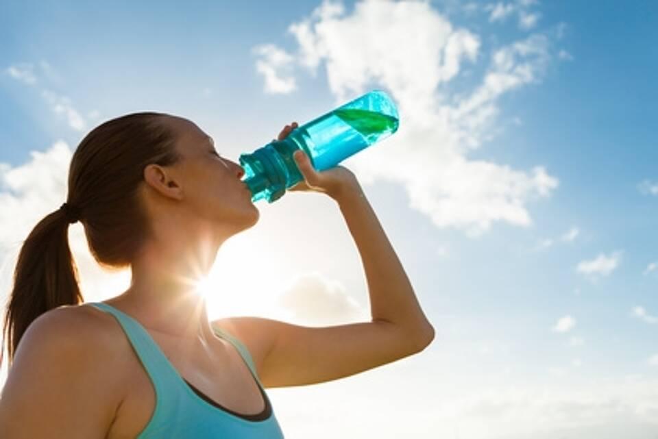sportlerin trinkt aus blauer Flasche