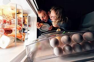 Papa und Tochter nachts vorm prall gefüllten, geöffneten Kühlschrank.