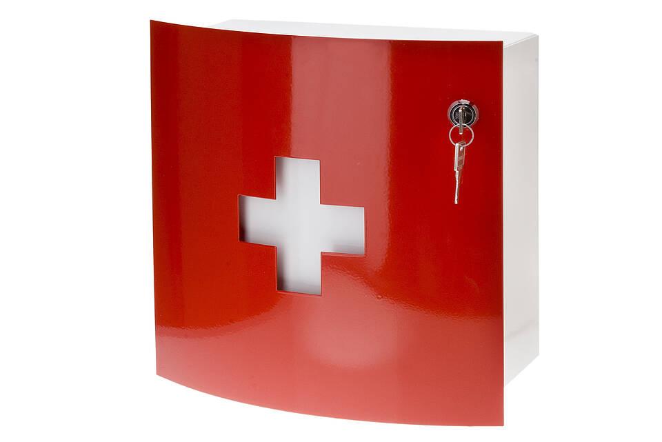 Hausapothekenschränkchen mit roter Tür und weißem Kreuz darauf.