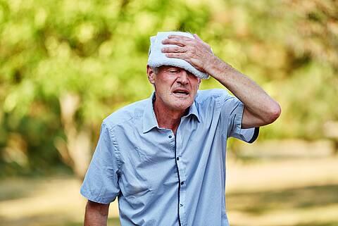 Alter Mann legt sich im Sommer zur Kühlung Waschlappen auf die Stirn.