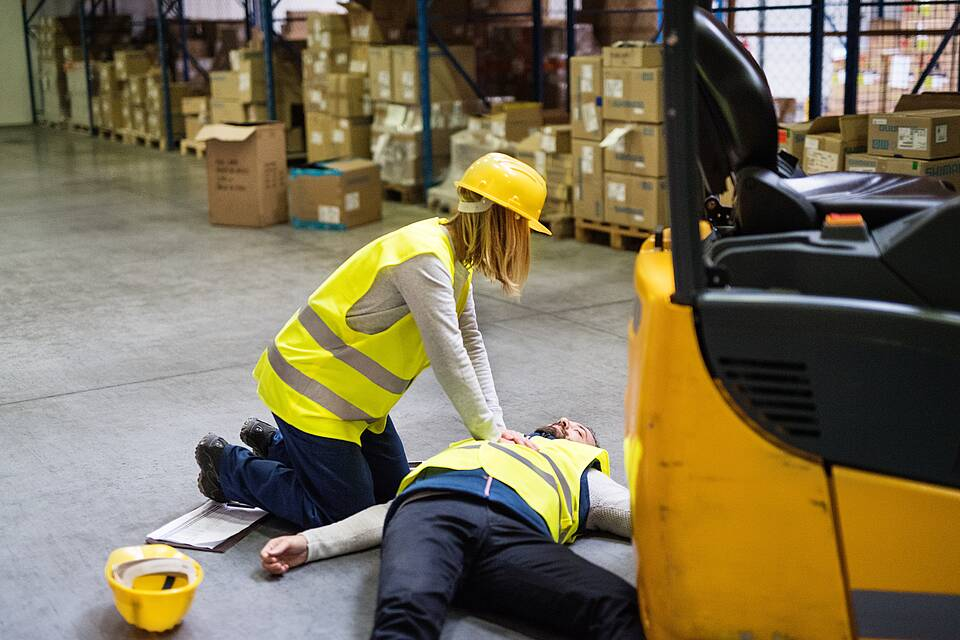 Arbeitsunfall: Mitarbeiterin mit gelbem Helm reanimiert Kollegen in Lagerhalle