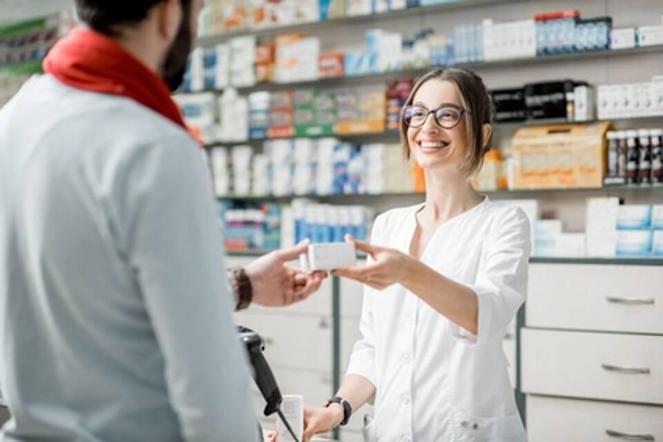 Apothekerin gibt Mann Medikamentenschachtel