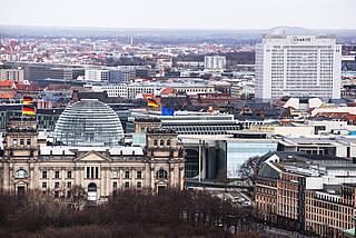 Weißes Charité-Bettenhaus in Berlin-Mitte mit Bundestag im Vordergrund.