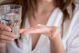 Frau nimmer weiße Tablette mit Glas Wasser ein (Antibiotikum)