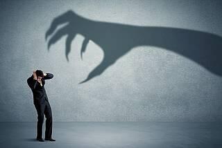 Mann in Schutzhaltung - Schatten einer Draculahand