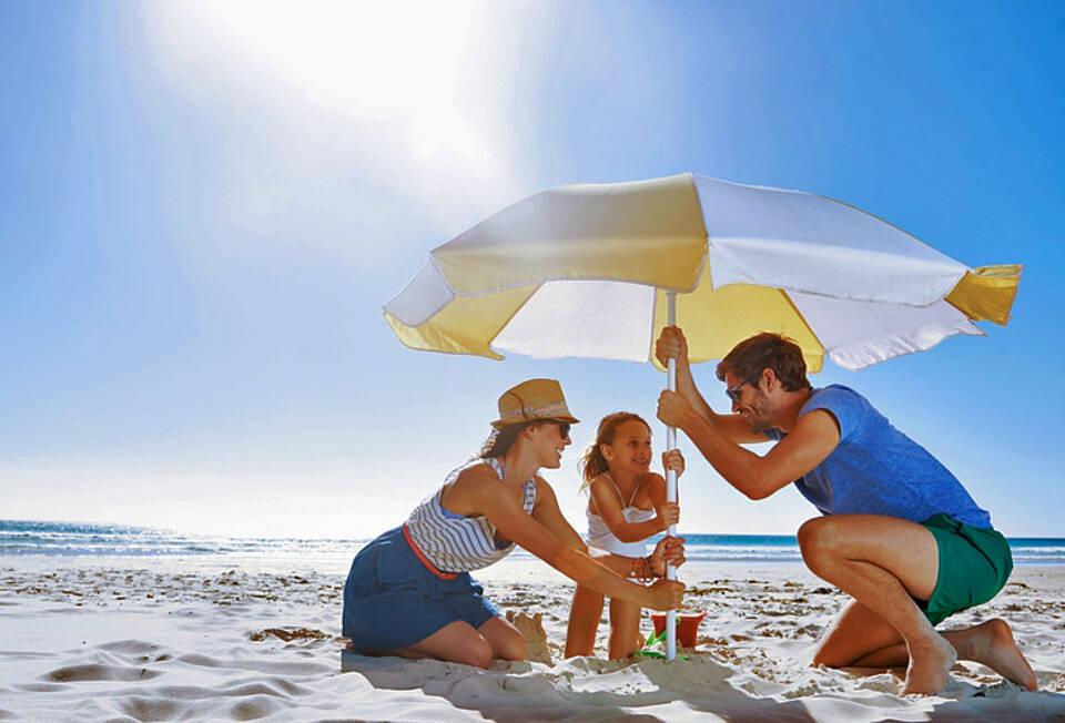 Familie am Sandstrand in der Sonne mit Sonnenschirmschirm