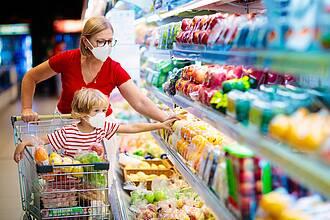 Kind mit Mama greifen ins Kühlregal im Supermarkt - mit weißen Corona-Mundschutzmasken im Gesicht.