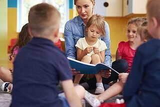 Kita-Kinder scharen sich um Erzieherin, die aus einem Buch vorliest.