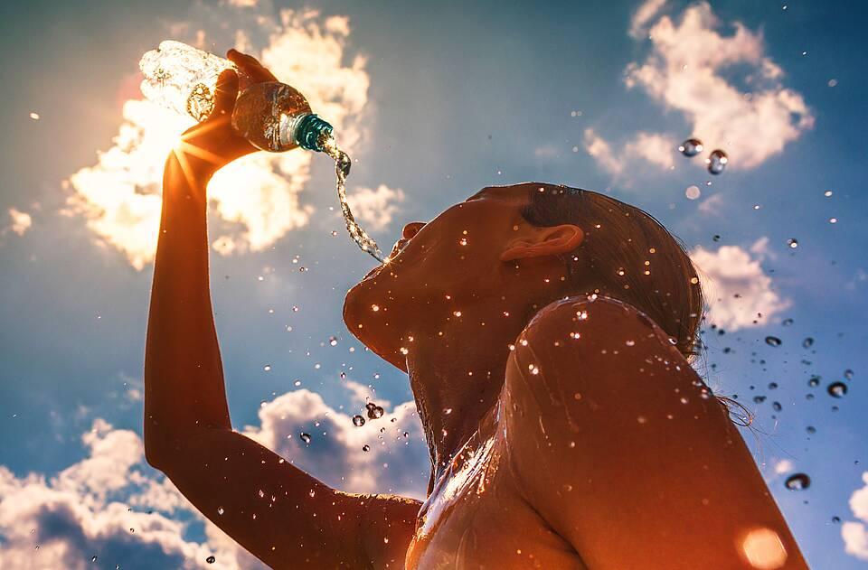 Sportlerin trinkt Wasser bei Sommerhitze und kühlt auch den Kopf damit ab.