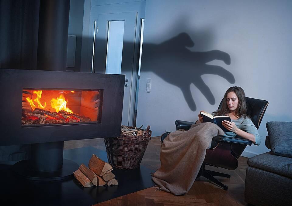 Frau im Wohnzimmersessel vorm Kaminofen, schwarze Kralle an der Wand
