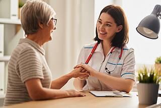 Junge Hausärztin hält älterer Patientin die Hand.