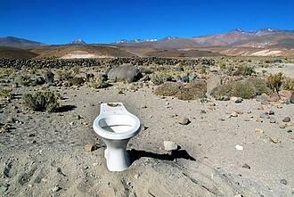 Weiße Toilettenschüssel steht einsam am Sandstrand