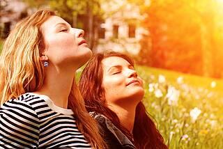 Zwei junge Frauen stecken ihre Nasen in die Frühlingssonne.
