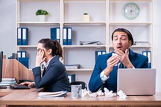 Mann hustet am Schreibtisch, Kollegin wendet sich ab