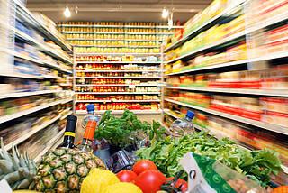 Supermarkt: Einkaufswagen mit Obst und Gemüse fährt Gang entlang, links und rechts Regale mit Lebensmitteln in Gläsern und Konserven.