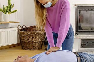 Frau mit Corona-Maske macht Herzdruckmassage bei Mann.