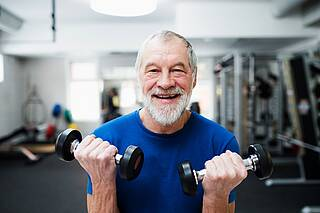 Mann mit grauem Bart und zwei Handhanteln im Kraftraum