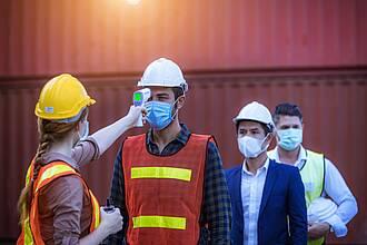 Frau mit gelbem Schutzhelm prüft mit Scannerpistole Firmenmitarbeiter auf erhöhte Temperatur.