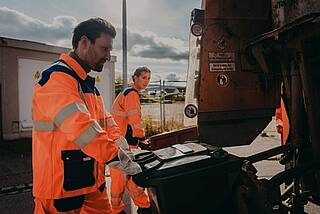 Müllmann+Müllfrau am Heck eines Müllautos bei bewölktem Himmel