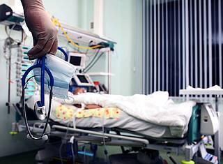 Krankenhaus - gestorbener Patienten, davor die Hand eines Arztes mit Stethoskop.