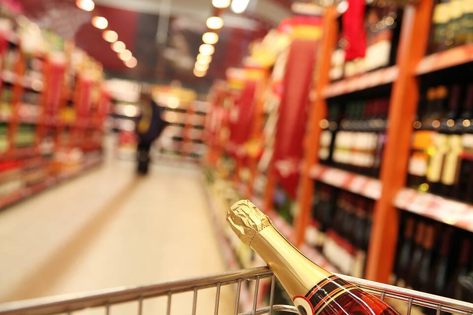 Flasche Sekt im Einkaufswagen - im Hintergrund Warenregale mit alkoholischen Getränken.