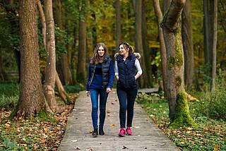 Zwei junge Frauen gehen im Wald nebeneinander spazieren.
