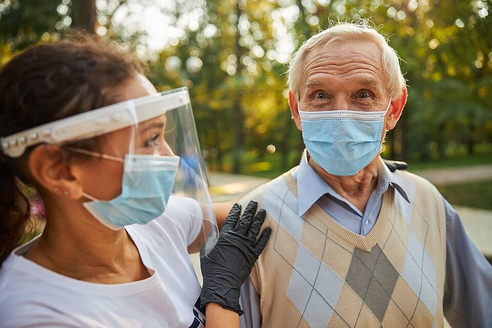 Altenpflegerin mit Corona-Maske und Plexiglas-Visier.
