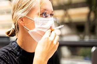 Frau raucht Zigarette durch Corona-Schutzmaske