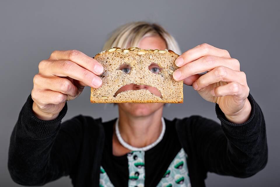 Glutenhaltige Lebensmittel. Frau hält sich Scheibe Brot vors Gesicht - mit eingeschnittenem Schmollmund.
