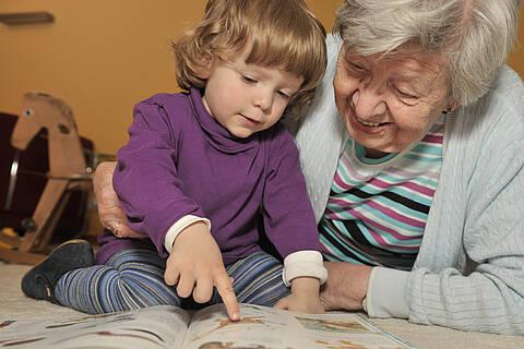 Oma und Enkelkind sehen sich zusammen ein Bilderbuch an.