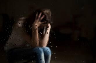 Frau stützt grübeln Kopf in die Hände - unscharf, hinter regennasser Glasscheibe