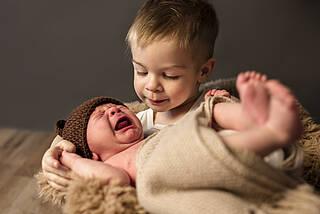 Kleiner Junge tröstet weinendes Baby-Geschwisterschen.