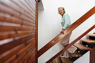 Alte Frau mit Stock geht glatte Holztreppe runter.