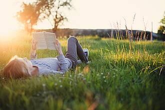 Jugendliche liegt rücklings auf einer Wiese und liest ein Buch, Abendsonnenschein.