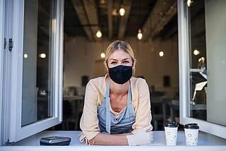 Frau mit Corona-Maske am offenen Fenster